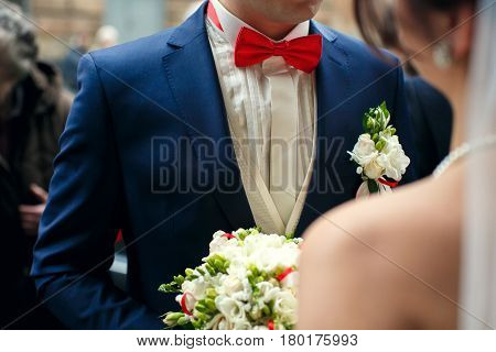 Groom in blue suit and red bow tie stands in the front of a bride