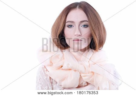 Girl in huge beige scarf around her neck on white backdrop. Red-haired woman looks at the camera. Big creme schawl. Isolated shot. Skin texture. Romance, theater. Emotion: lovely, tenderness