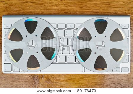 Two compact discs in the form of a retro reel lie on the keyboard, top view