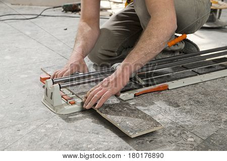 Real construction worker cutting ceramic tiles using ceramic cutter.
