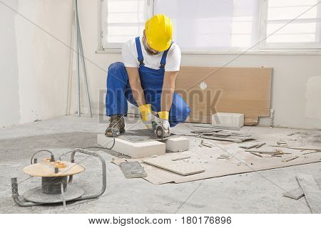 Construction worker cutting tile using angle grinder.