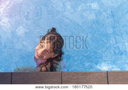 Areal view of cute little girl playing in the swimming pool