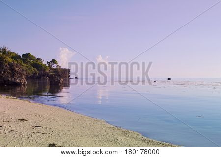 Tropical landscape with bright sky and greenery. Pink and blue toned photo. Fantastic dream scenery with empty sand beach. Seaside with white sand beach and clear still water. Exotic place for holiday