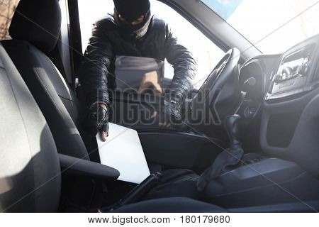 Thief stealing tablet from car