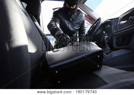 Thief stealing handbag from car