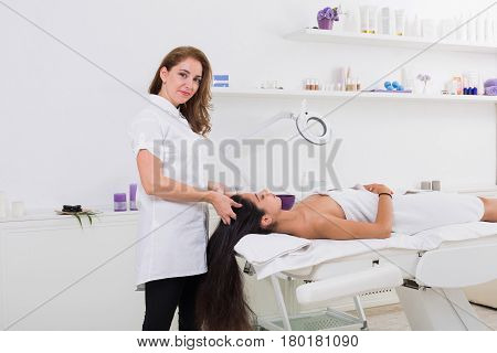 Woman beautician doctor with patient in spa wellness center. Portrait of a young female professional cosmetologist make head massage to beautiful brunette girl in cosmetology cabinet or beauty parlor.