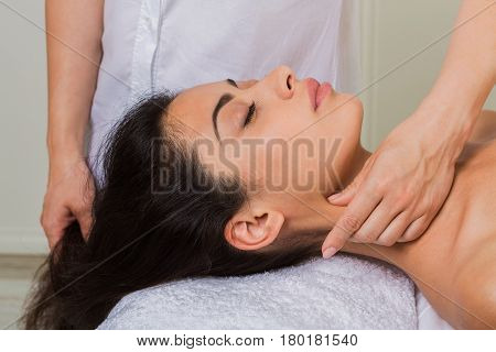 Relaxing neck massage in spa to beautiful indian girl. Cosmetology cabinet or beauty parlor. Professional masseur therapist with client