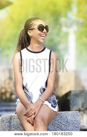 Natural Portrait of Happy Positive African American Teenager Girl With Long Dreadlocks in Sunglasses. In Front of Fountain Outdoors.Vertical image