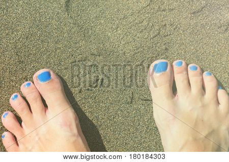Female feet on white sand. Sandy beach by tropical seaside vintage background. Summer vacation in paradise banner template. Feet of woman on white sand beach toned photo. Sunny day on exotic island