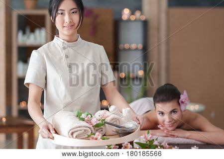 Beautiful Asian masseur holding tray with spa therapy products in wellness center