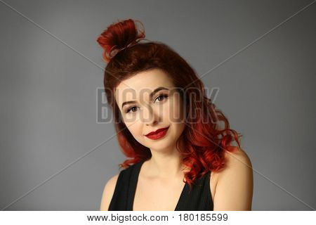 Beautiful young woman with dyed curly hair on color background