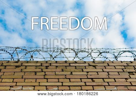 Inscription Freedom . Barbed wire on a brick wall against a blue sky with clouds.