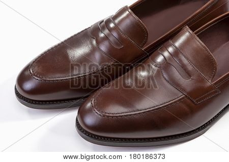Footwear Concepts. Extreme Closeup of Leather Stylish Brown Penny Loafer Shoes Tips Against White Background. Horizontal Image Orientation