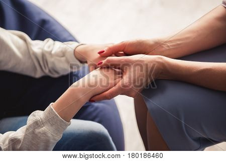 Teenage girl at the psychotherapist. Cropped image of doctor holding girl's hands