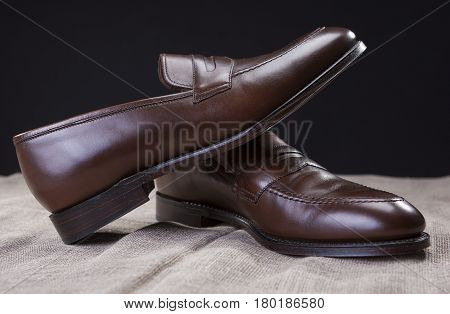 Shoes Concepts and Ideas. Closeup of Stylish Modern Brown Leather Penny Loafer Shoes Against Black Background. Horizontal Image