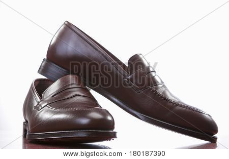 Footwear Concepts. Closeup of Pair of Stylish Brown Penny Loafer Shoes Against White. Placed on Wooden Reflecting Surface. Horizontal Shot