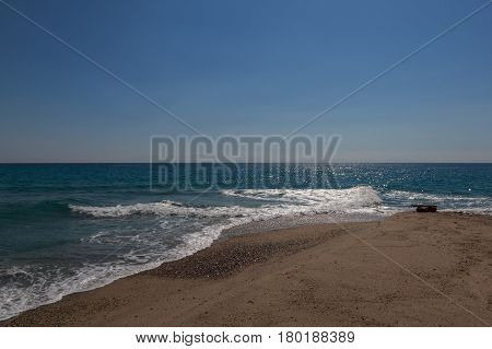 The Surf Of The Blue Turquoise Sea With White Perpendicular Waves On The Sandy Beach Against A Brigh