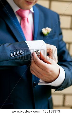 The groom adjusts cufflinks on the shirt against a brick wall background