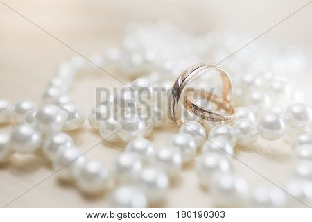 A pair of bright wedding rings with diamonds lying on beads of pearls on a light background