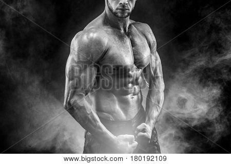Strong bodybuilder with six pack. Man with perfect abs, shoulders, biceps, triceps and chest, personal fitness trainer flexing his muscles in smoke