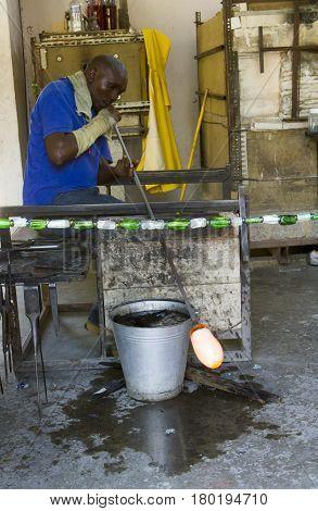 Arusha Tanzania - March 3 2017 : Craftsman blowing glass in artisan workshop in Tanzania Africa.