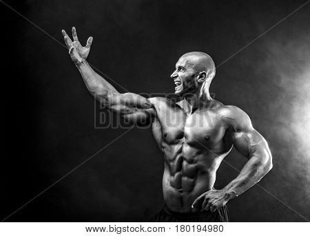 Bald handsome man, muscular topless body holding arm up with anger. Isolated.