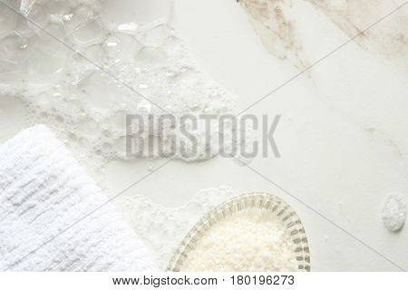 White marble bathroom counter with soap suds, washcloth and bath salts. Copy space.