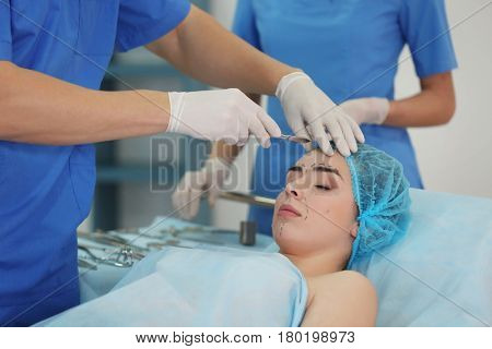 Plastic surgeon operating patient in clinic