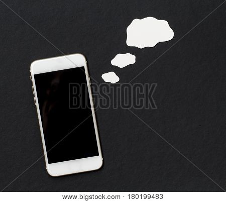 White phone with blank though bubble on black background. Smartphone with black screen banner template. Mobile phone and empty cloud. Flat lay composition with cartoon element cut out from white paper