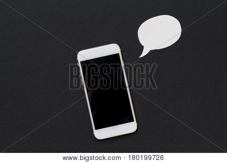 White phone with blank speech bubble on black background. Smartphone with black screen banner template. Mobile phone and text bubble. Flat lay composition with cartoon element cut out from white paper