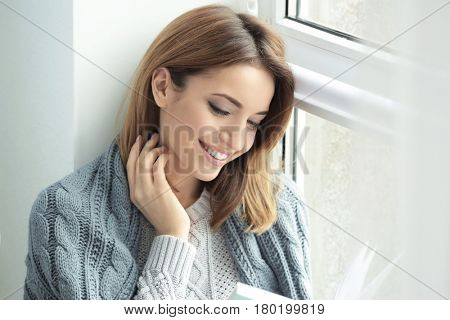 Beautiful young woman reading book while resting near window at home