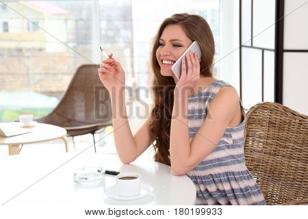 Young woman smoking and speaking on telephone in light room