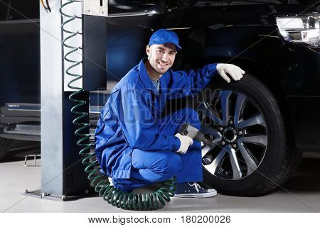 Young mechanic changing wheel in car service