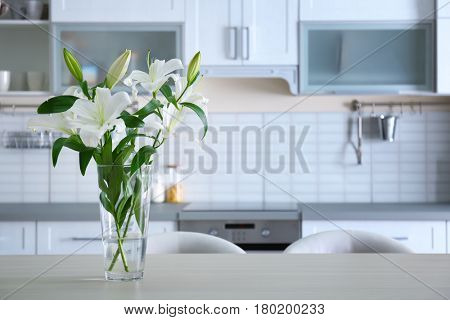 Beautiful white lilies in vase on kitchen table