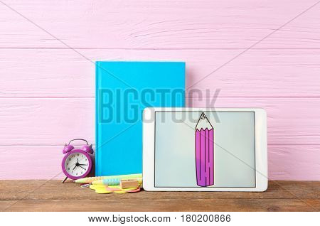 Tablet and stationery on wooden table
