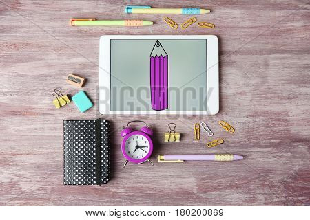 Tablet and stationery on wooden background