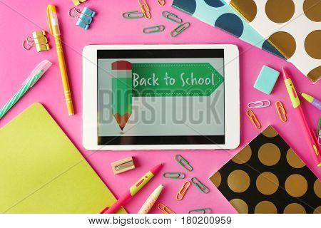 Tablet with BACK TO SCHOOL message and stationery on pink background