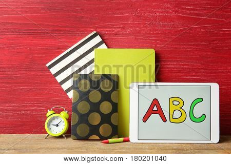 Tablet with ABC message and stationery on wooden table