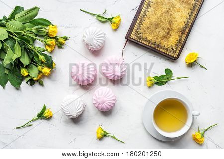modern home office with flowers, marsh-mallow and copybook in spring concept on light marble desk background top view