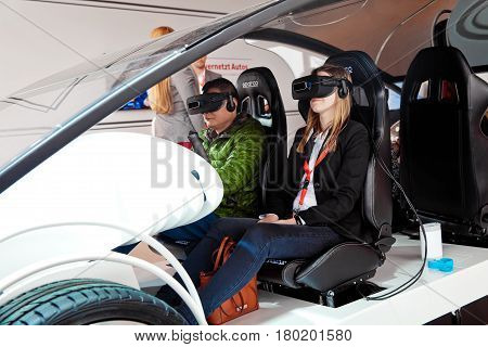 Hannover, Germany - March, 2017: Girl in virtual glasses headset testing Vodafone 5G-based communications systems for vehicles on exhibition Cebit 2017 in Hannover Messe, Germany