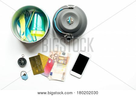 Preparation for traveling with mobile, credit cards and sunglasses on white desk background top view