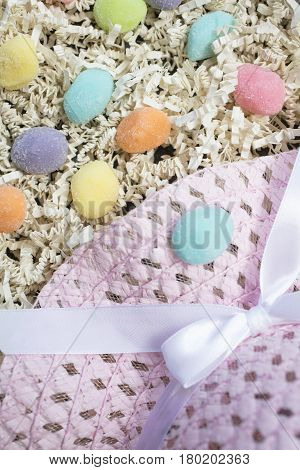 Pink Easter hat laying on a bed of confetti with pink blue yellow purple and orange gummy eggs