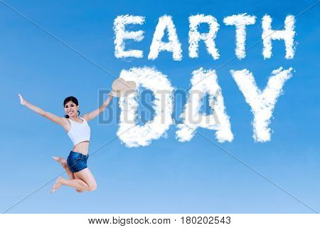 Earth Day concept. Happy young woman leaping on the sky with cloud shaped Earth Day word