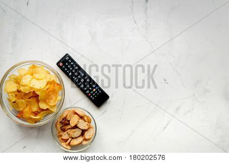 watching movies concept with chips and zapper on white table background top view mock up