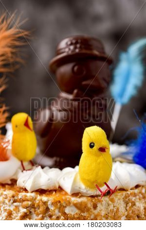 a mona de pascua, a cake eaten in Spain on Easter Monday, topped with a chocolate chick and some yellow teddy chicks and decorated with feathers of different colors