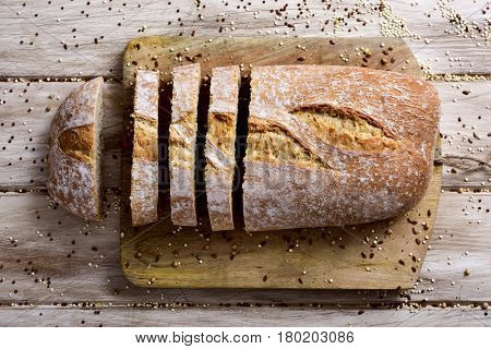 high-angle shot of a loaf of spelt bread cut in some slices on a chopping board, placed on a white rustic wooden table