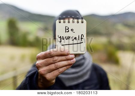 closeup of a young caucasian man wearing a scarf and a knit cap in a natural landscape showing a notepad with the text be yourself written in it