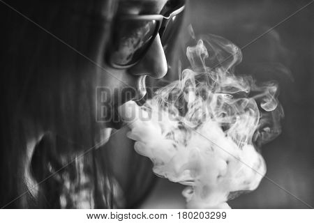 Vape. Young Handsome White Girl In Sunglasses Is Admiting Puffs Of Steam From The Electronic Cigaret