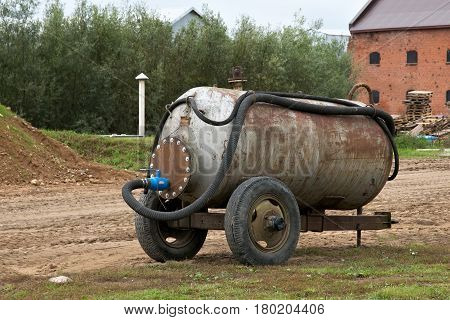 Old rusty water tank on the wheels.