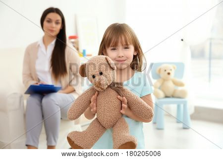 Little girl with teddy bear and child psychologist on background